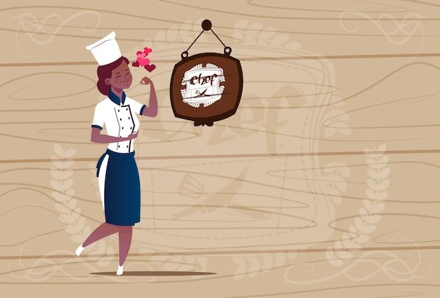 Cozinheiro chefe americano africano feminino cozinheiro chefe sorridente feliz dos desenhos animados em uniforme de restaurante sobre fundo texturizado de madeira