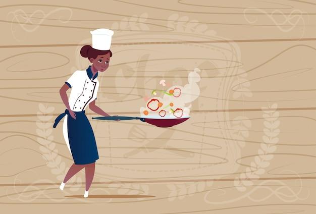 Cozinheiro chefe americano africano feminino segurando cartoon de fritura no restaurante uniforme sobre fundo texturizado de madeira