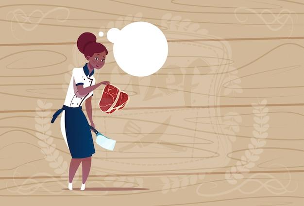 Cozinheiro chefe americano africano feminino segurando o chefe de desenho animado de carne no restaurante uniforme sobre fundo texturizado de madeira