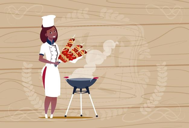 Cozinheiro chefe americano africano feminino segurando o chefe dos desenhos animados de kebab em uniforme de restaurante sobre fundo texturizado de madeira