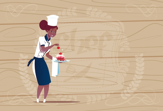 Cozinheiro chefe americano africano feminino segurando o chefe dos desenhos animados de sobremesa em uniforme de restaurante sobre fundo texturizado de madeira
