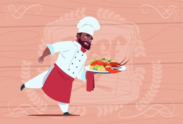 Cozinheiro chefe americano africano, segurando a bandeja com a lagosta, sorrindo chefe dos desenhos animados branco de restaurante, com o uniforme sobre o fundo texturizado de madeira