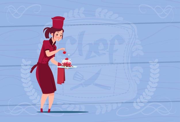 Cozinheiro chefe feminino cozinhar segurando o chefe dos desenhos animados de sobremesa em uniforme de restaurante sobre fundo texturizado de madeira