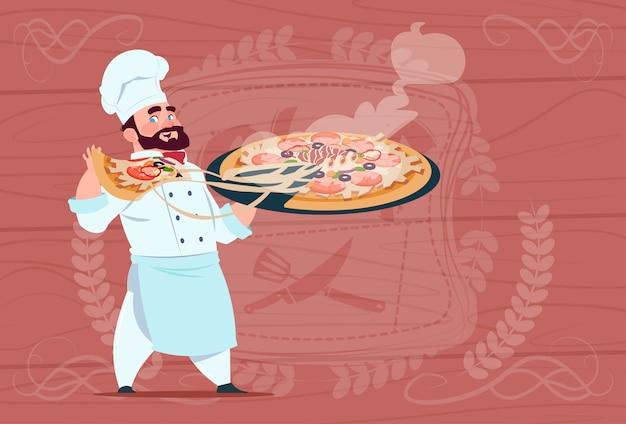 Cozinheiro chefe segurando pizza sorrindo chefe dos desenhos animados em branco restaurante uniforme sobre fundo texturizado de madeira