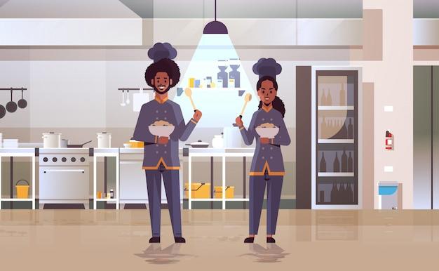 Cozinheiros casal chefs profissionais segurando placas com mingau trabalhadores afro-americanos em pratos de degustação uniformes, cozinhando o conceito de alimentos restaurante moderno cozinha interior apartamento comprimento total horizontal