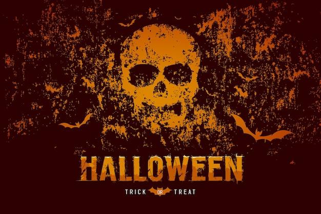 Crânio de halloween e morcego em uma superfície áspera de fundo laranja e preto