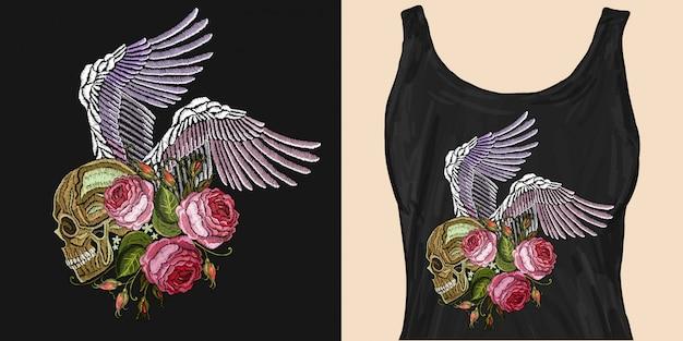 Crânio humano bordado, asas de anjo e rosas