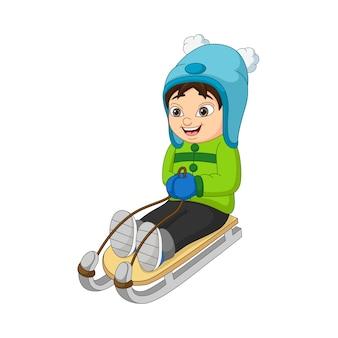 Criança adorável descendo a colina de trenó
