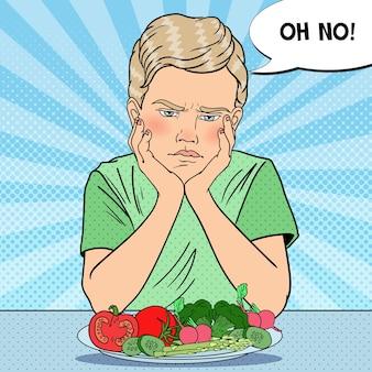 Criança chateada com prato de legumes frescos