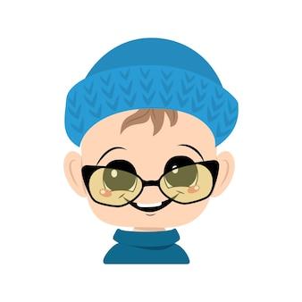 Criança com olhos grandes e sorriso largo em um chapéu de malha azul e óculos criança fofa com um rosto alegre em ...