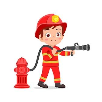 Criança feliz e fofa vestindo uniforme de bombeiro e segurando uma mangueira