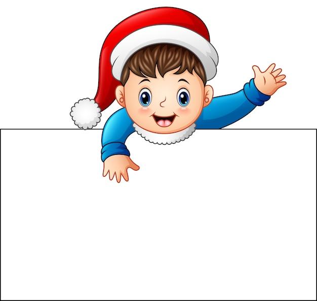 Criança feliz usando gorro de papai noel segurando cartaz em branco
