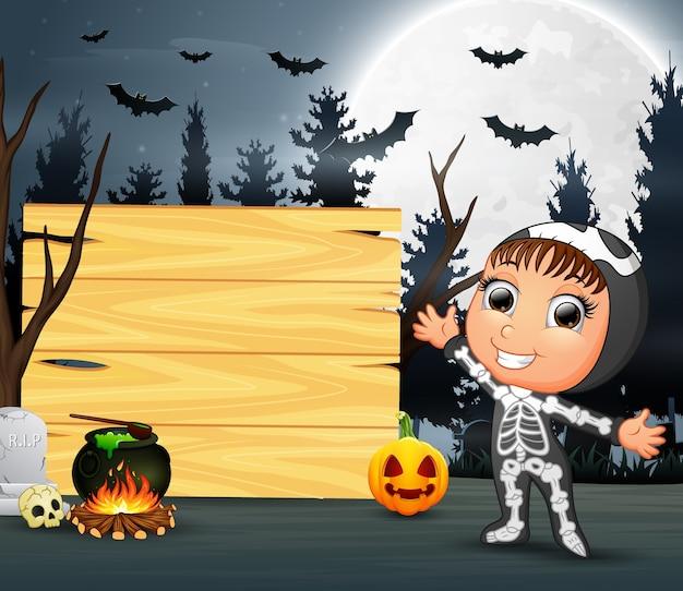 Criança feliz vestindo fantasia de esqueleto ao lado da placa de madeira