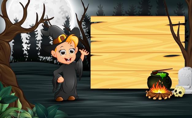Criança feliz vestindo traje de bruxa fica ao lado da placa de madeira