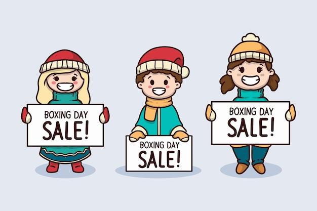 Criança fofa com roupas de inverno segurando banner de venda do dia de boxe
