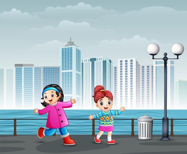 Crianças alegres felizes andando no parque da cidade
