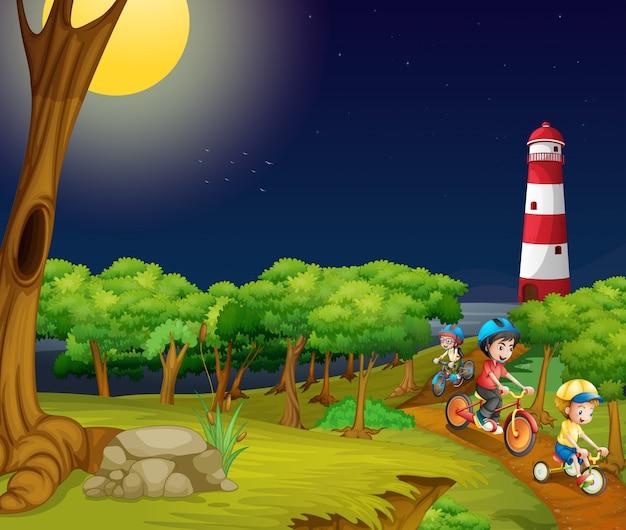 Crianças andando de bicicleta no parque à noite