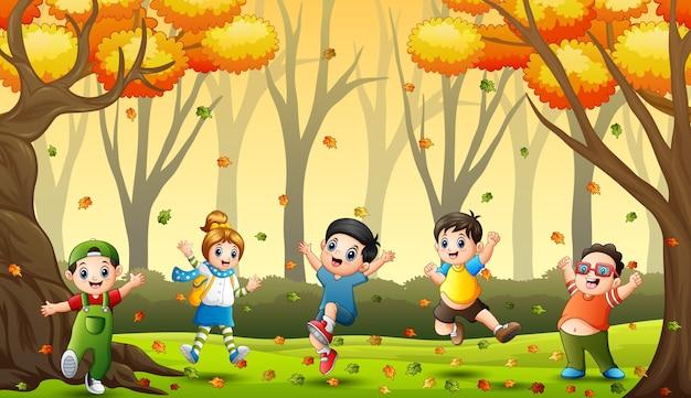 Crianças brincando com folhas caídas na floresta de outono