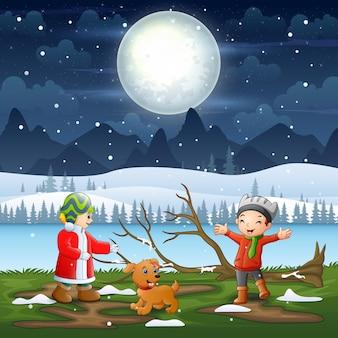 Crianças brincando na paisagem noturna de inverno