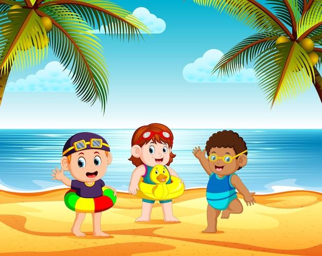 Crianças brincando na praia e usando o pneu no dia brilhante