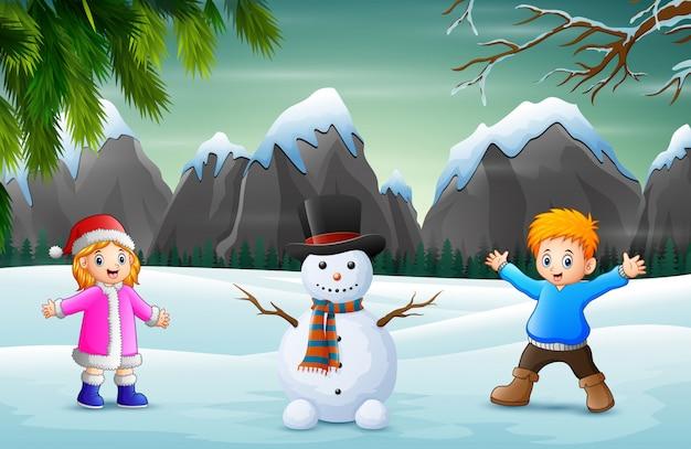 Crianças com boneco de neve na paisagem de neve