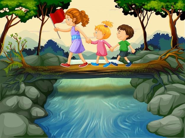 Crianças cruzando o rio na floresta