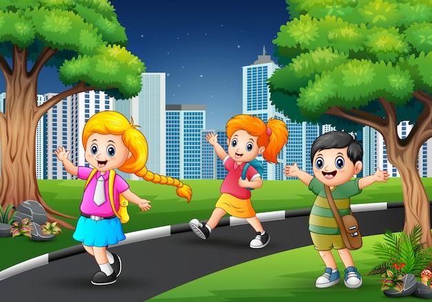 Crianças de escola felizes andando na estrada para a cidade