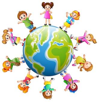 Crianças de escola felizes em pé ao redor da terra