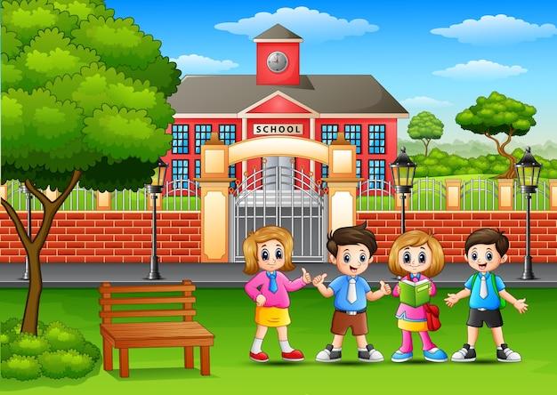 Crianças de escola felizes em pé fora da frente do prédio da escola
