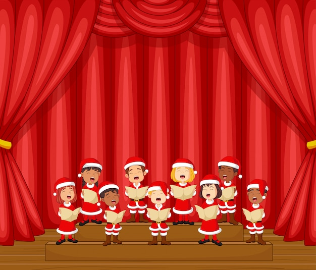 Crianças do coro cantando uma música no palco com fantasia de papai noel
