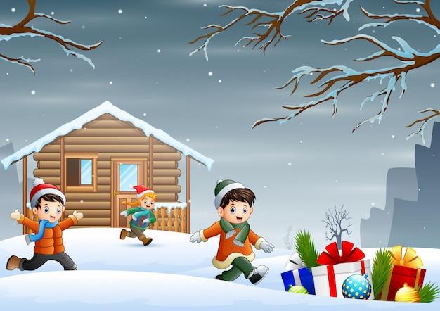 Crianças dos desenhos animados, aproveitando o natal de inverno em frente à casa