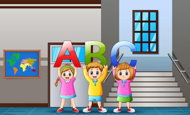 Crianças dos desenhos animados segurando alfabetos na frente da turma