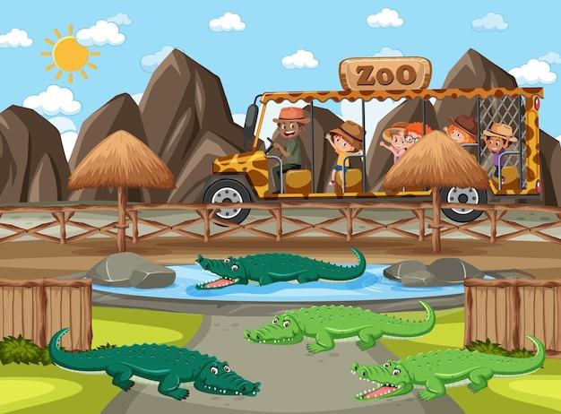 Crianças em carro de turismo observando grupo de crocodilos na cena do zoológico