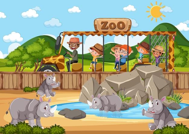 Crianças em carro de turismo observando grupo de rinocerontes na cena do zoológico