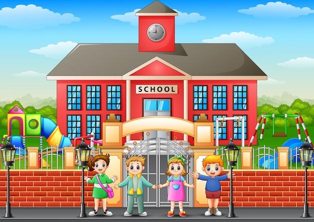 Crianças em idade escolar feliz em pé na frente do prédio da escola