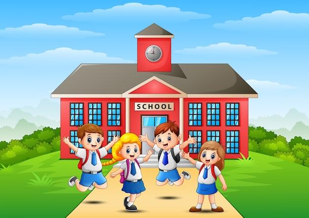 Crianças em idade escolar felizes em frente ao prédio da escola