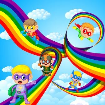 Crianças em roupa de herói voando sobre o arco-íris