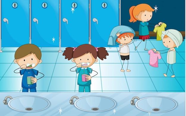 Crianças escovando dentes e ficando vestidos no vestiário