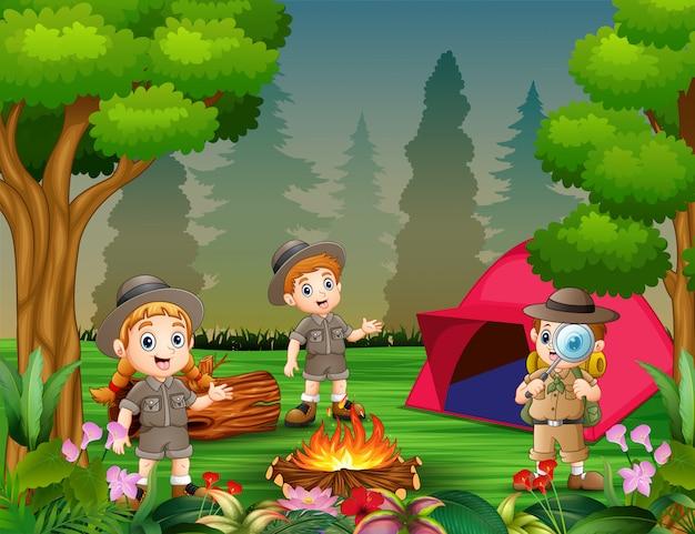 Crianças felizes acampadas na floresta bonita