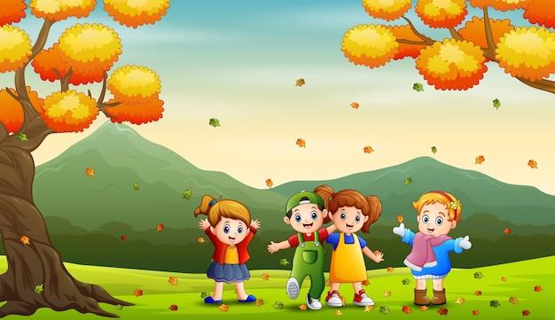 Crianças felizes brincando ao ar livre no outono