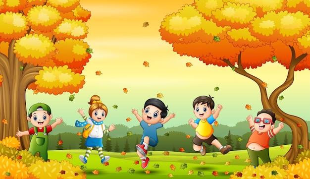 Crianças felizes brincando com folhas caídas