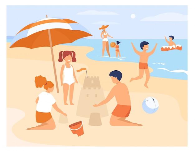 Crianças felizes brincando na praia de areia à beira-mar