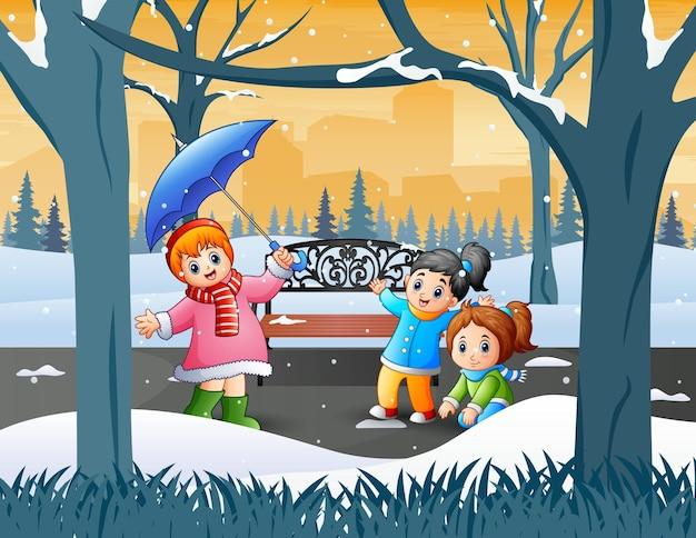 Crianças felizes brincando no parque de inverno