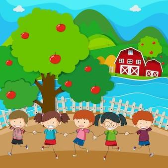 Crianças felizes brincando no pomar de maçã