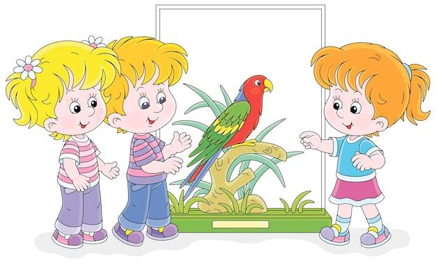 Crianças felizes caminhando em um jardim zoológico e observando um papagaio tropical engraçado com uma plumagem colorida brilhante e um desenho de cauda longa