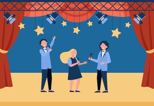 Crianças felizes com microfones no palco, desempenhando papéis no teatro da escola ou cantando.