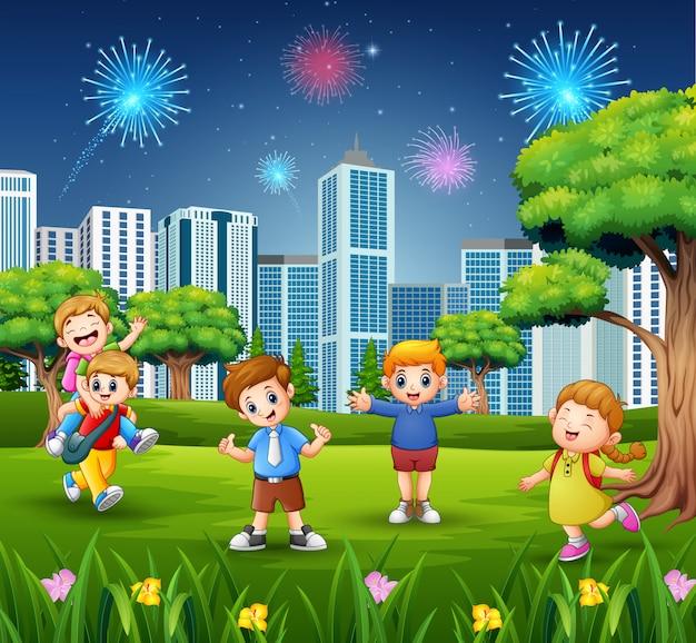 Crianças felizes da escola no parque da cidade com fogo de artifício