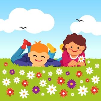 Crianças felizes, deitado na grama do campo do prado
