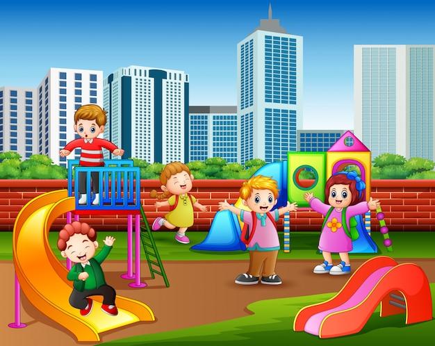Crianças felizes do jardim de infância que jogam no campo de jogos