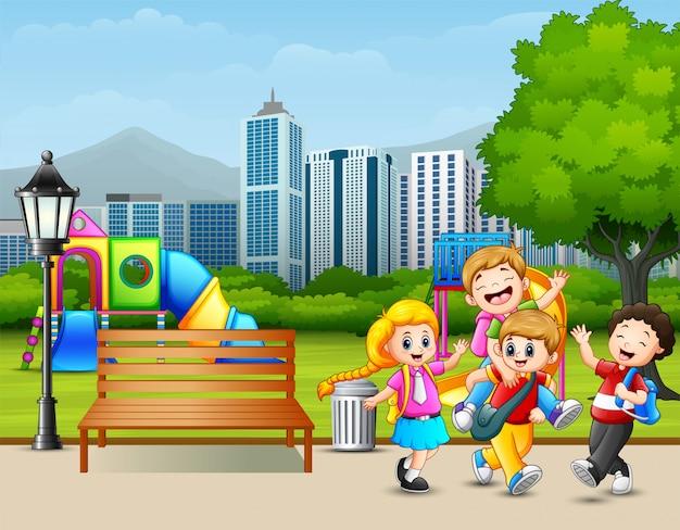Crianças felizes dos desenhos animados que jogam no parque da cidade